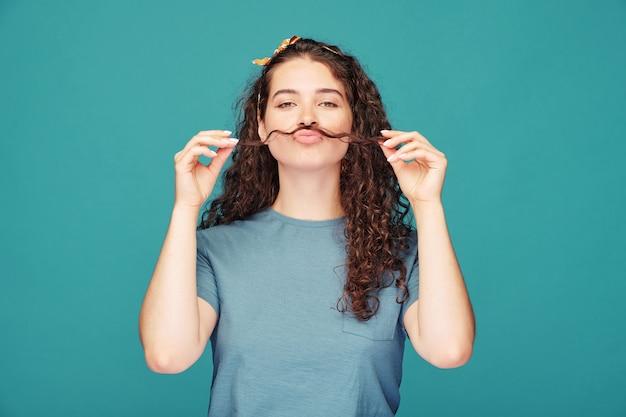 Zabawna dziewczyna z długimi ciemnymi włosami trzymając go między nosem a ustami podczas zabawy na niebieskiej ścianie