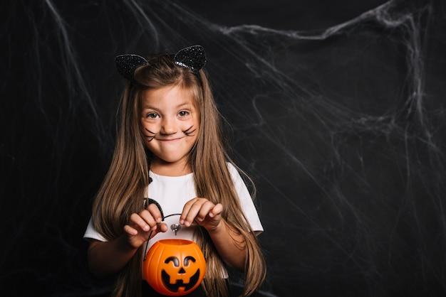 Zabawna dziewczyna z kocie uszy i wiadro cukierek albo psikus