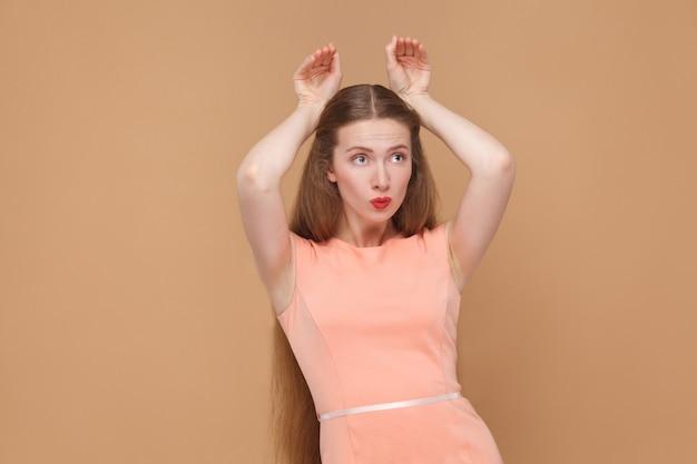 Zabawna dziewczyna z rękami w stylu królika. portret emocjonalnej słodkie, piękne kobiety z makijażem i długimi włosami w różowej sukience. kryty, studio strzał, na białym tle na jasnobrązowym lub beżowym tle.