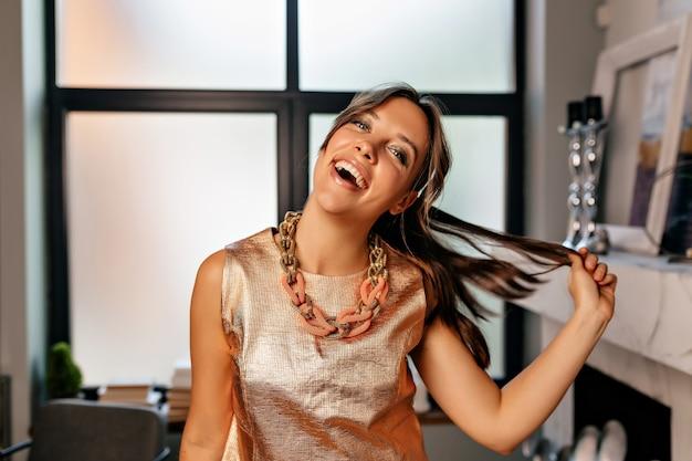 Zabawna dziewczyna z szczęśliwymi emocjami ubrana w połyskliwą koszulkę i złoty naszyjnik