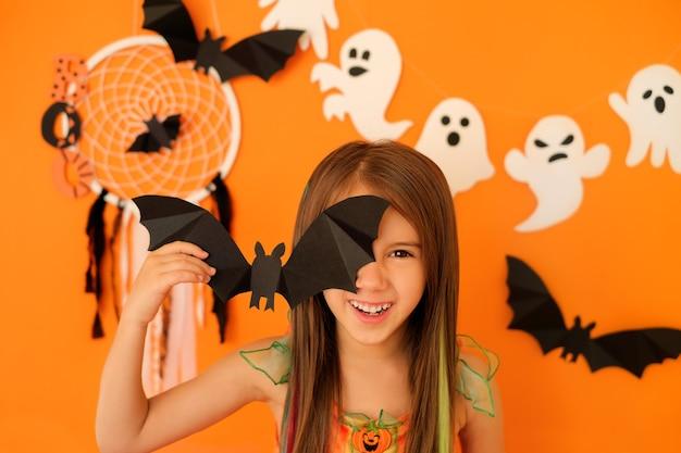 Zabawna dziewczyna ze śmiechem i złym spojrzeniem trzyma w rękach nietoperza zakrywającego nim jedno oko