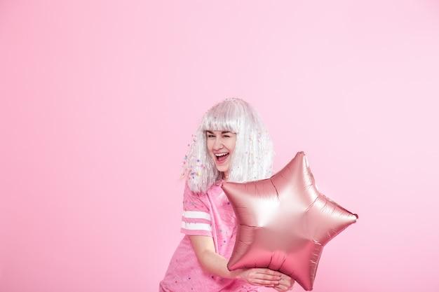 Zabawna dziewczyna ze srebrnymi włosami daje uśmiech i emocje na różowym tle. młoda kobieta lub dziewczyna z balonami i konfetti