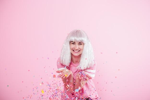 Zabawna dziewczyna ze srebrnymi włosami daje uśmiech i emocje na różowym tle. młoda kobieta lub dziewczyna z konfetti