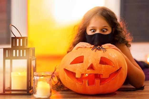 Zabawna dziewczyna ze zdziwieniem patrzy na pająka na pomarańczowej dyni