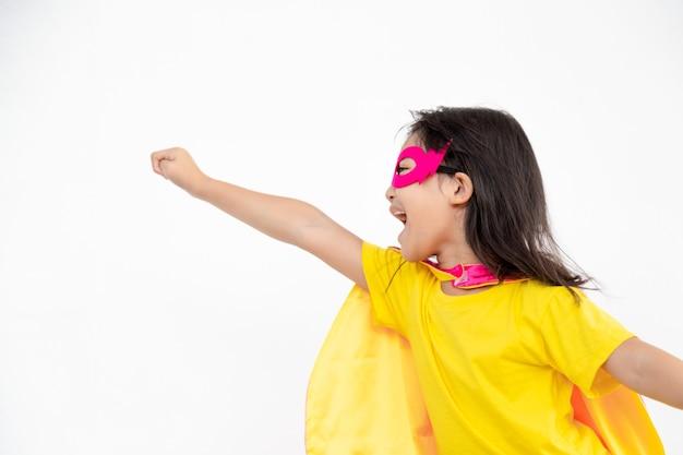 Zabawna dziewczynka gra moc super bohatera na białym tle. koncepcja superbohatera.