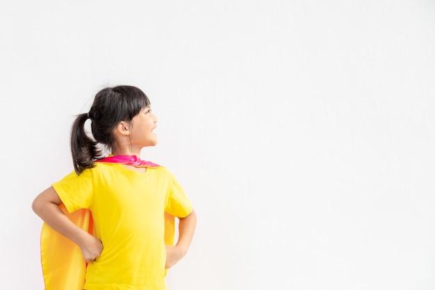 Zabawna dziewczynka gra superbohatera moc na białym tle. koncepcja superbohatera.