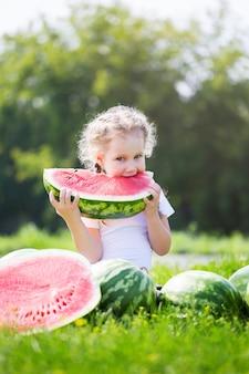 Zabawna dziewczynka jedzenie arbuza na zewnątrz w ciepły i słoneczny letni dzień. koncepcja zdrowego odżywiania.