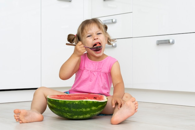 Zabawna dziewczynka jedzenie arbuza z dużą łyżką, siedząc na podłodze w kuchni