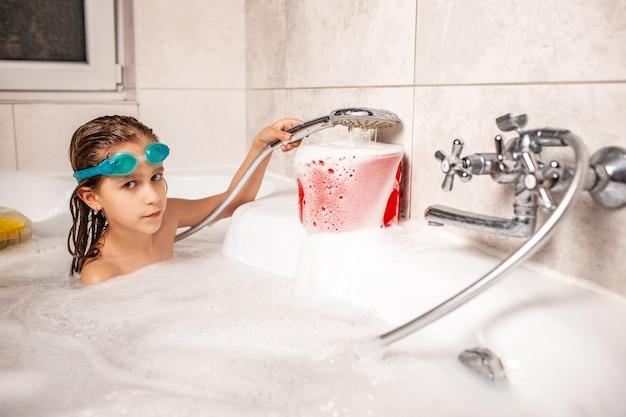 Zabawna dziewczynka kąpie się w wannie i wlewa wodę do białej piany spod prysznica