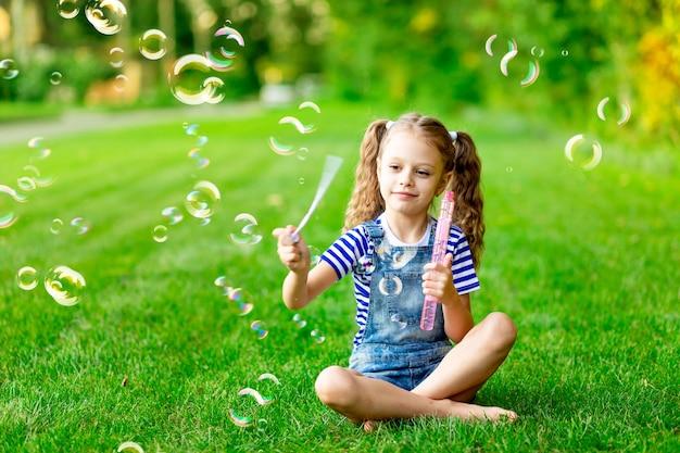 Zabawna dziewczynka latem na trawniku z baniek mydlanych na zielonej trawie, zabawy i radości, miejsca na tekst