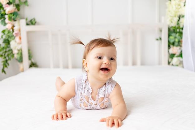 Zabawna dziewczynka sześć miesięcy czołganie się w jasnym, pięknym pokoju na białym łóżku w koronkowym body i uśmiechnięta