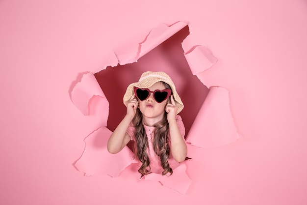Zabawna dziewczynka wyglądająca z dziury w czapce plażowej i okularach w kształcie serca na kolorowym tle, miejsce na tekst, strzelanie studyjne