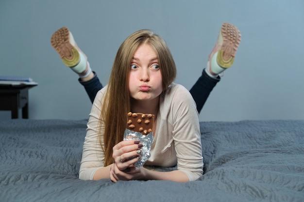 Zabawna emocjonalna dziewczyna trzyma w ręku mleczną czekoladę z całymi orzechami