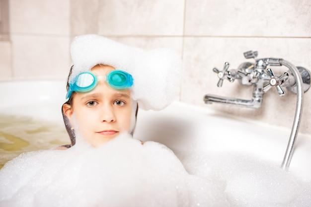 Zabawna, emocjonalna dziewczynka kaukaska myje głowę dużą ilością piany w łazience w domu.