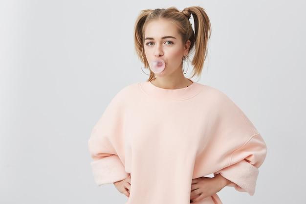Zabawna figlarna jasnowłosa nastolatka z dwoma kucykami ubrana w różowy sweter z długimi rękawami o radosnym wyrazie, z bąbelkiem gumy do żucia w ustach, na białym tle