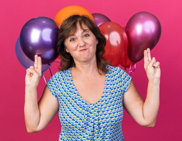 Zabawna i radosna kobieta w średnim wieku w imprezowym kapeluszu z kolorowymi balonami bawi się
