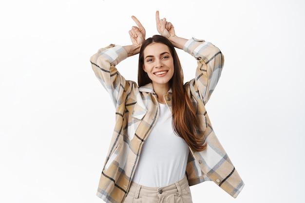 Zabawna i szczęśliwa dorosła kobieta bawiąca się, pokazująca gest rogów diabła byka i uśmiechająca się pozytywnie, uparta lub zdeterminowana, stojąca nad białą ścianą