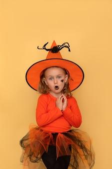 Zabawna impreza z okazji halloween dzieci zaskoczona emocjonalna dziewczynka w pomarańczowym kostiumie i kapeluszu czarownicy na halloween!