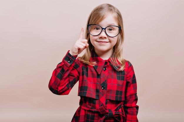 Zabawna, inteligentna dziewczynka nosi okulary i kraciastą koszulę podniesioną do góry jednym palcem i uśmiecha się z przodu
