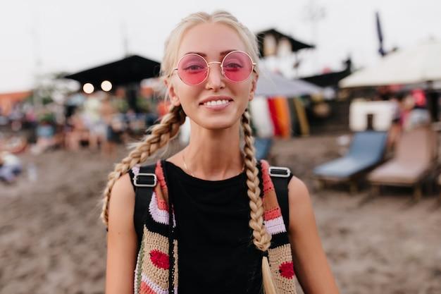 Zabawna jasnowłosa kobieta z warkoczykami, pozowanie na rozmycie tła plaży. plenerowy portret beztroskiej blondynki w modnym stroju nosi różowe okulary przeciwsłoneczne.