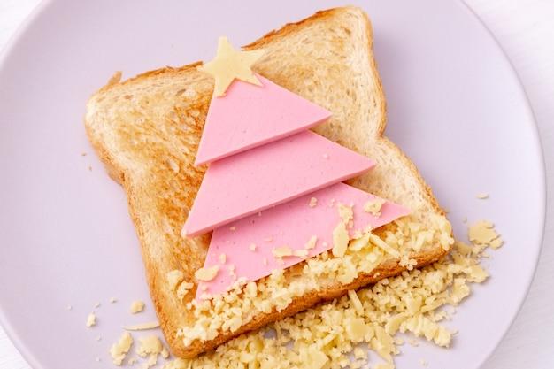 Zabawna kanapka z jadalną choinką z tostów, kiełbasy i sera