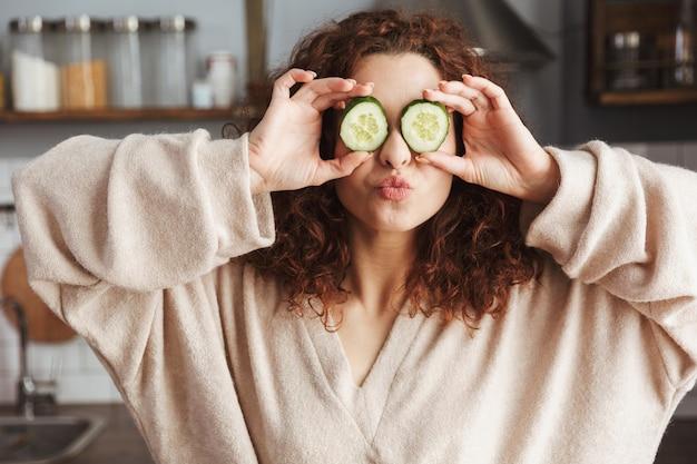 Zabawna kaukaska kobieta bawiąca się podczas gotowania sałatki ze świeżymi warzywami w kuchni w domu