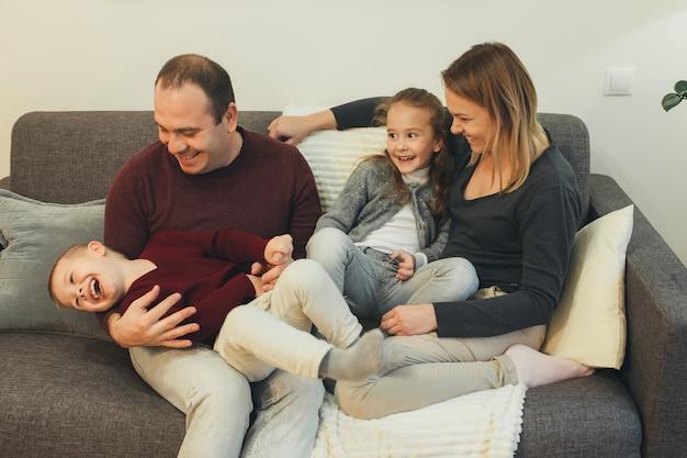 Zabawna, kaukaska rodzina składająca się z 4 członków, siedząca na sofie i bawiąca się razem, uśmiechając się radośnie
