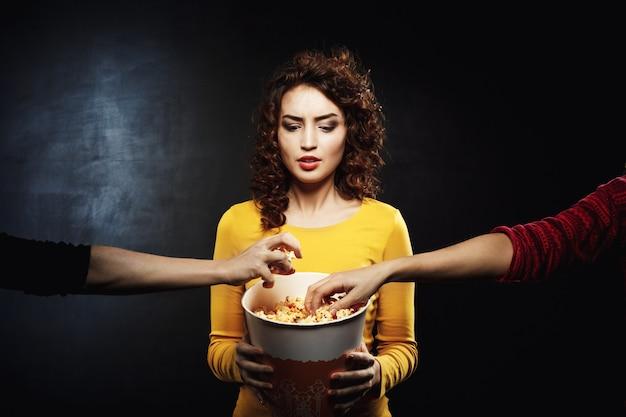 Zabawna kobieta nie lubi dzielić się przekąskami z przyjaciółmi w kinie