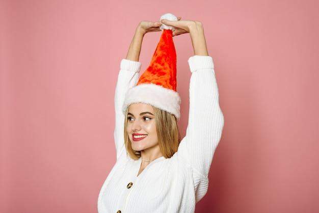 Zabawna kobieta trzyma pompon w santa hat i patrząc w kamerę na różowym tle. uśmiechnięta szczęśliwa kobieta.