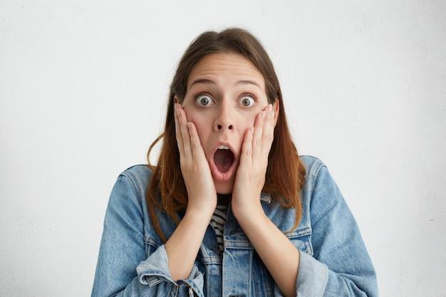 Zabawna kobieta trzymająca ręce na policzkach i krzycząca z pełnym niedowierzaniem, trzymając szeroko otwarte usta i wyskakujące oczy, zszokowany wygląd z powodu wysokich cen sprzedaży