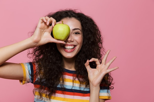 Zabawna kobieta w wieku 20 lat z kręconymi włosami, uśmiechnięta i trzymająca zielone jabłko odizolowane na różowo