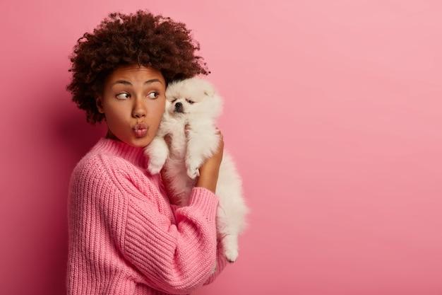 Zabawna kobieta z kręconymi włosami ma złożone usta, cieszy się wolnym czasem z uroczym miniaturowym szczeniakiem, trzyma szpica blisko twarzy