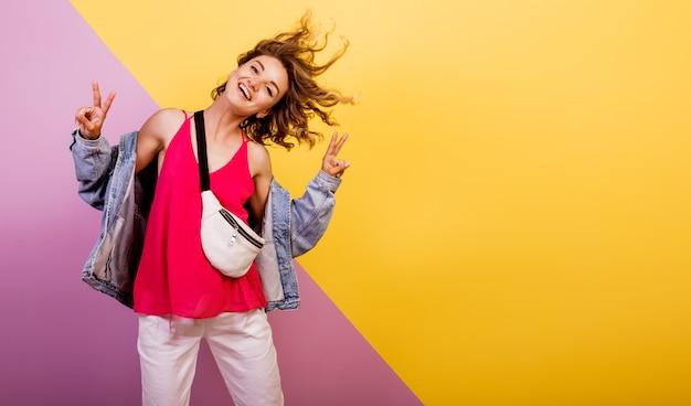 Zabawna kobieta z krótkimi falującymi włosami, taniec i zabawa na wielokolorowym.