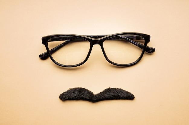 Zabawna kompozycja z okularami i wąsami na beżu