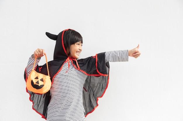 Zabawna koncepcja halloweenowego dziecka, mała urocza dziewczyna z kostiumem halloweenowym duchem przerażającym, który trzyma pod ręką pomarańczowego ducha dyni, na białym tle