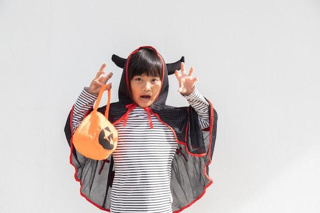 Zabawna koncepcja halloweenowego dziecka mała urocza dziewczyna z kostiumem halloweenowym duchem strasznym
