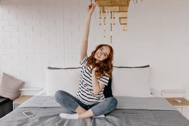 Zabawna ładna dziewczyna w dżinsach pozowanie w sypialni. wspaniała rudowłosa dama siedząca na łóżku.