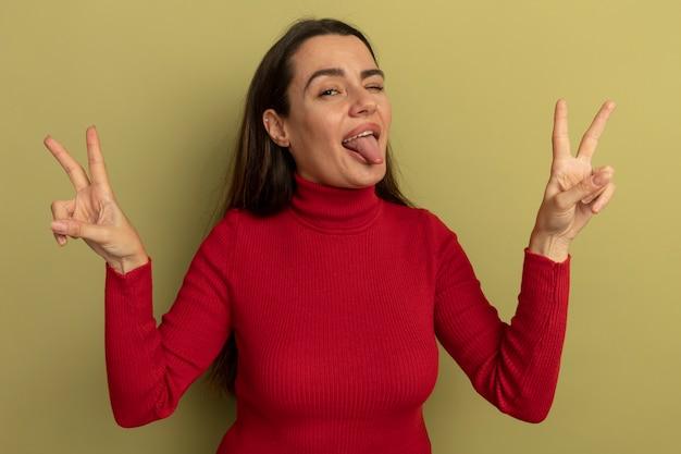 Zabawna ładna kaukaska kobieta mruga okiem wystawiającym język i gestem ręki znak zwycięstwa na oliwkowej zieleni