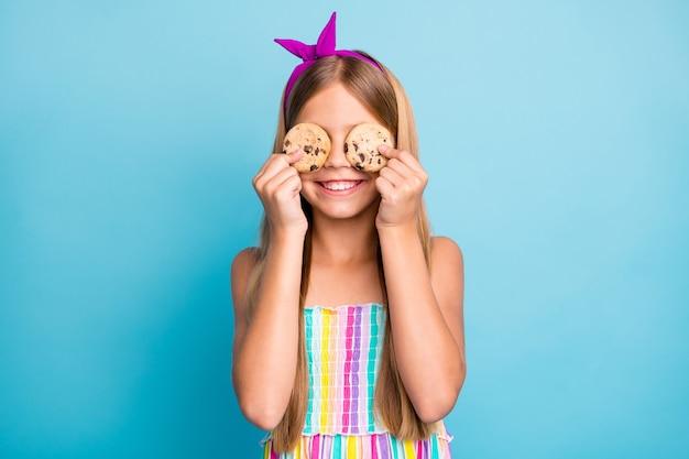Zabawna ładna urocza urocza mała dziewczynka jedzą ciasteczka, cieszą się lunchem