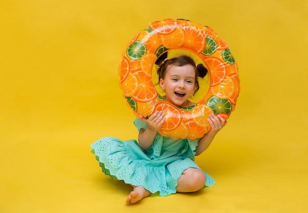 Zabawna mała dziewczynka bawi się nadmuchiwanym kółkiem do pływania na żółtym tle z kopią przestrzeni
