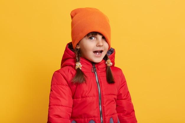 Zabawna mała dziewczynka pozuje na białym tle na żółtej ścianie z szeroko otwartymi ustami, naciągnij czapkę na jedno oczy
