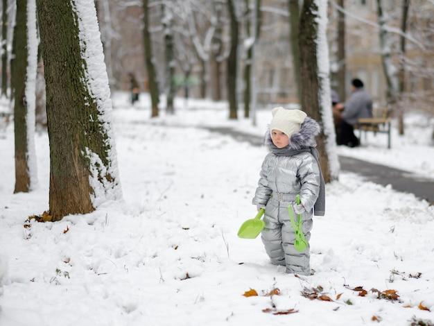 Zabawna mała dziewczynka w ciepłym srebrnym kombinezonie trzyma łopatę do zabawy