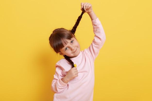 Zabawna mała dziewczynka wciągająca się w warkocze i patrząc prosto w kamerę z uroczym uśmiechem, ubrana w jasnoróżową koszulkę, urocze dziecko na żółtej ścianie.