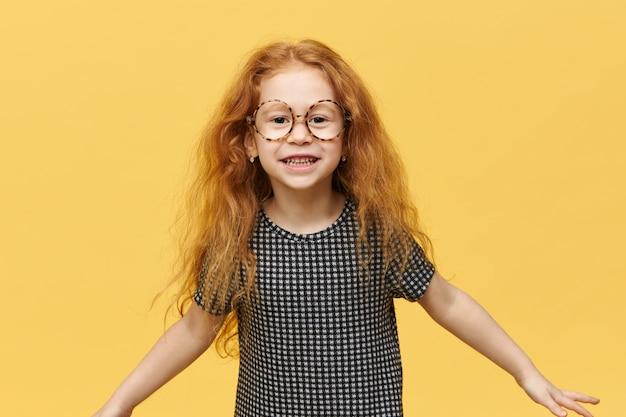 Zabawna mała dziewczynka z długimi, luźnymi rudymi włosami, skacząca, wyrażająca prawdziwe pozytywne emocje, uśmiechnięta szeroko w dużych okrągłych okularach. obraz słodkie dziecko wesoły zabawy pozowanie na białym tle