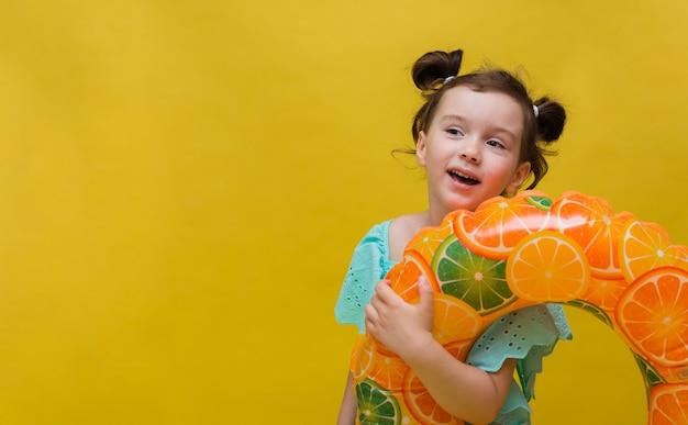 Zabawna mała dziewczynka z nadmuchiwanym kółkiem na żółtym tle z miejscem na tekst