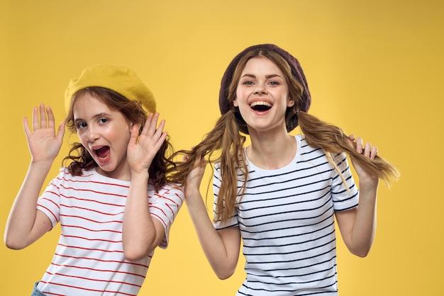 Zabawna mama i córka w kapeluszach moda zabawa radość rodzinna żółte tło