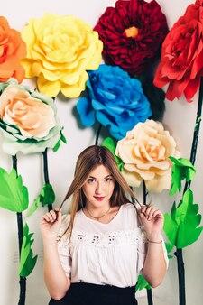 Zabawna młoda dziewczyna siedzi na podłodze w studio na tle dużych sztucznych kwiatów.
