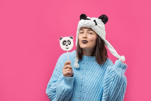 Zabawna młoda dziewczyna stojąca z pysznym lizakiem panda w ręku i kapeluszem na głowie na różowym tle.