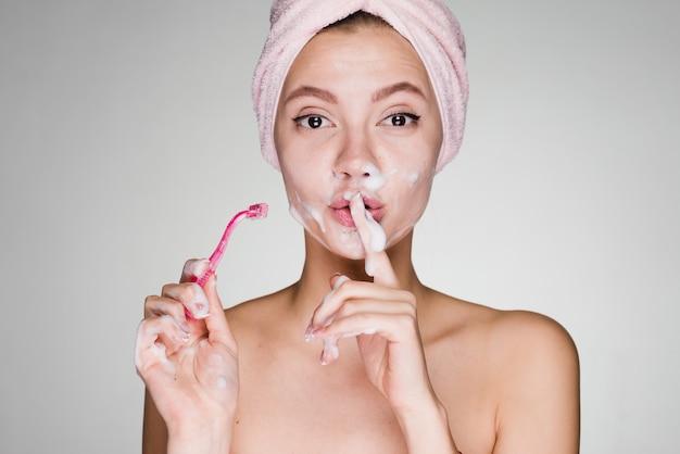 Zabawna młoda dziewczyna z ręcznikiem na głowie przykłada palec do ust, goli twarz jak mężczyzna