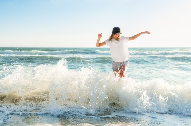 Zabawna młoda kobieta figlarny na plaży o zachodzie słońca. piękna szczęśliwa kobieta nad brzegiem błękitnego morza, bawiąc się bryzgami wody, pozytywny nastrój, letnie wakacje, słoneczna koncepcja